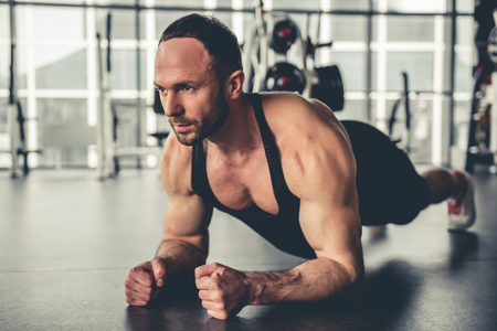 laying abs exercise: Handsome muscular man is doing plank exercise while working out in gym Stock Photo