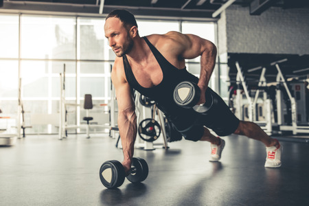 laying abs exercise: Handsome muscular man is working out with dumbbells in gym