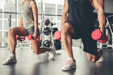 매력적인 스포츠 사람들이 체육관에서 아령으로 운동하고 있습니다.