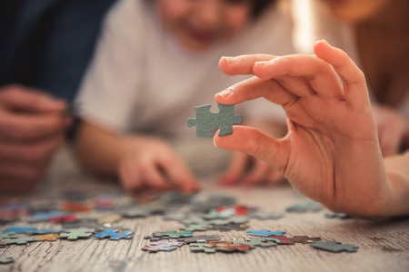 Little girl and her young parents are doing jigsaw puzzle while lying on the floor at home Banco de Imagens