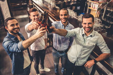 Handsome guys are clinking bottles of beer, looking at camera and smiling while resting in pub