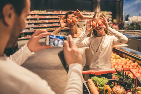 Handsome dad is taking photo of his beautiful cheerful wife and daughter while they are doing shopping in the supermarket