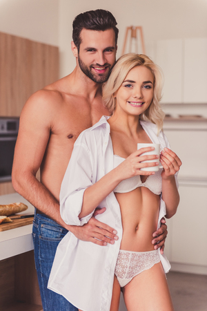 half naked: Beautiful young half-naked couple is looking at camera and smiling while hugging in kitchen Stock Photo