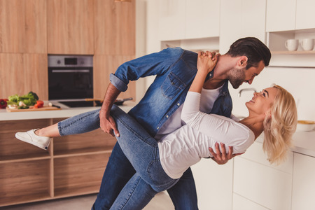 Beautiful young couple is looking at each other and smiling while dancing in kitchen