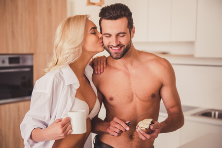 Beautiful couple in kitchen in the morning. Girl is drinking coffee and kissing her shirtless boyfriend in cheek while he is making sandwiches