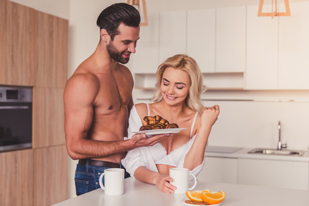 half naked: Beautiful young half-naked couple is smiling while having a breakfast in kitchen in the morning