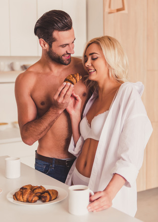 half naked: Beautiful young half-naked couple is eating croissants, drinking coffee and smiling while having a breakfast in kitchen in the morning Stock Photo