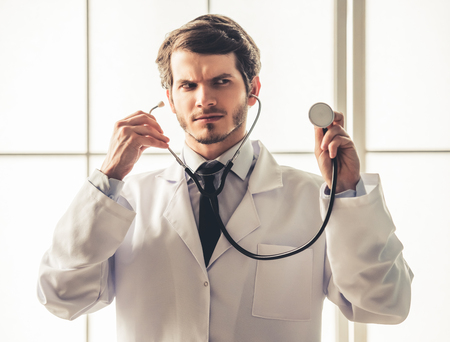 sound therapist: Handsome young doctor in white coat is using a stethoscope while working in office