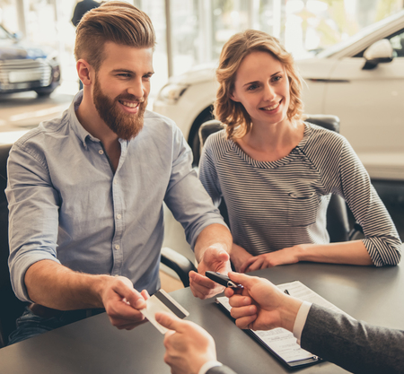 finance manager: Visiting car dealership. Beautiful couple is talking to sales manager, paying with credit card and smiling Stock Photo