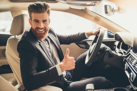 Handsome bearded businessman is showing Ok sign, looking at camera and smiling while sitting in a new car in car dealership Фото со стока