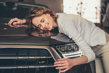 中古車販売店を訪問します。美しい若い女性は、彼女の新しい車を抱き締めると笑みを浮かべて 写真素材