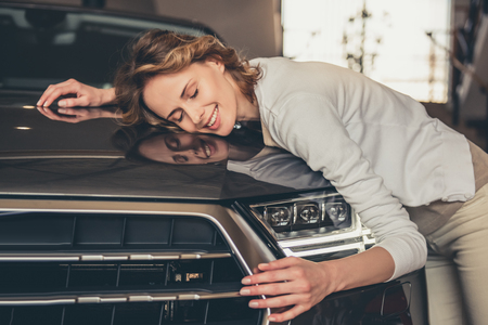 Bezoekende autohandelaar. Mooie jonge vrouw knuffelt haar nieuwe auto en glimlacht