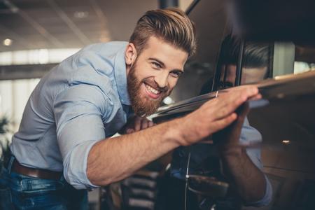 中古車販売店を訪問します。ハンサムなひげを生やした男は彼の新しい車をなでると笑みを浮かべて