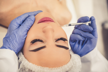 Beautiful young woman is getting an injection in face while lying with closed eyes at the cosmetician, close-up