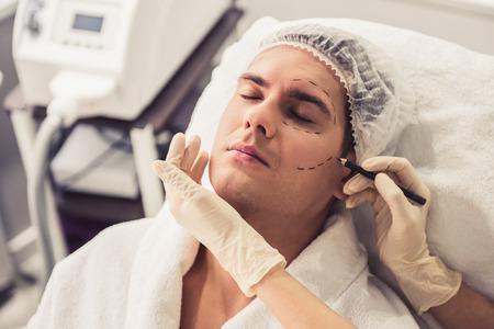 El hombre hermoso está sentándose en el cosmetician mientras que el doctor en guantes médicos está examinando su cara usando un lápiz