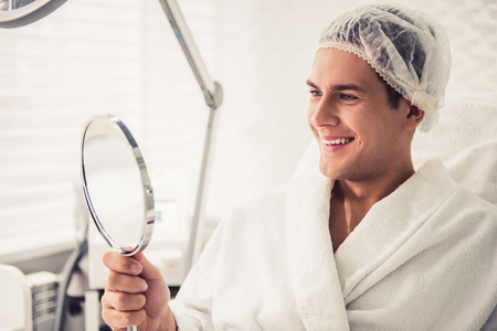 Handsome man is looking into the mirror and smiling while sitting at the cosmetician