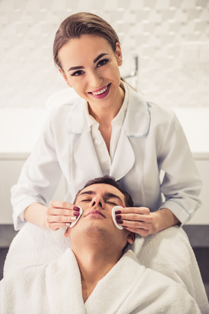 lift hands: Handsome man is getting face skin treatment. Beautiful cosmetician is smiling while clearing patients face Stock Photo