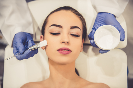 Beautiful young woman is getting face skin treatment. Doctor in medical gloves is applying cream on her face using a brush