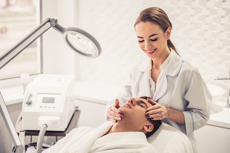 Handsome man is getting face skin treatment. Beautiful cosmetician is examining his face and smiling Stock Photo