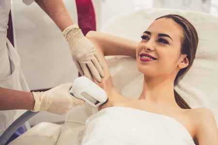 Beautiful young woman is smiling while doctor in medical gloves is undertaking the laser epilation of her armpits Archivio Fotografico