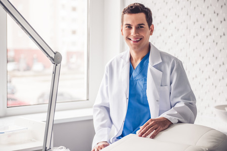 Handsome young doctor in white coat is looking at camera and smiling while standing in office