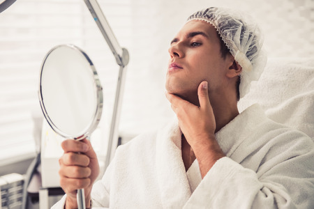 Handsome man is looking into the mirror and examining his chin while sitting at the cosmetician Stock Photo