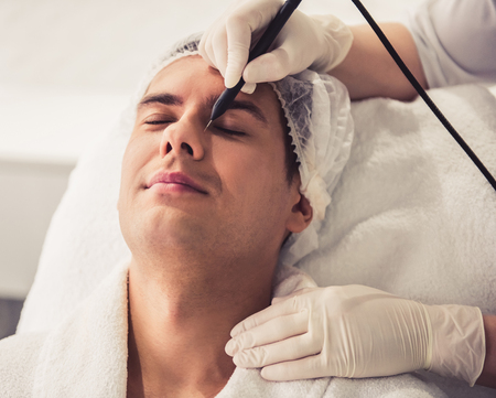 Handsome man is getting face skin treatment. Doctor in medical gloves is undertaking the procedure using modern equipment