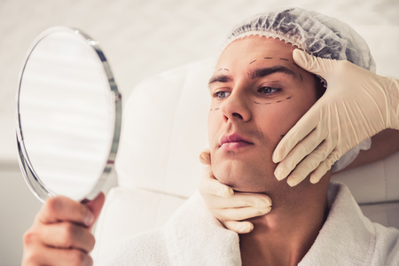 Handsome man is looking into the mirror at the cosmetician while doctor in medical gloves is examining his face