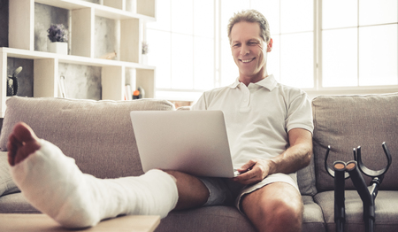 Handsome mature man with broken leg in gypsum is using a laptop and smiling while sitting on sofa at home