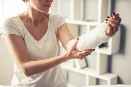 美しい熟女は、traumatologist で座っている石膏で彼女の腕の画像をトリミング 写真素材
