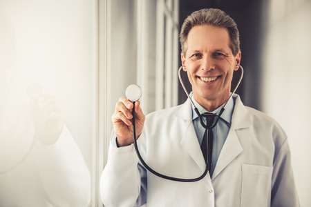 sound therapist: Handsome mature doctor in white coat is holding a stethoscope, looking at camera and smiling while standing in hospital corridor