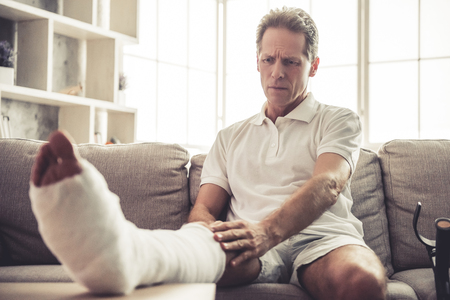 Handsome mature man is touching his broken leg in gypsum while sitting on sofa at home