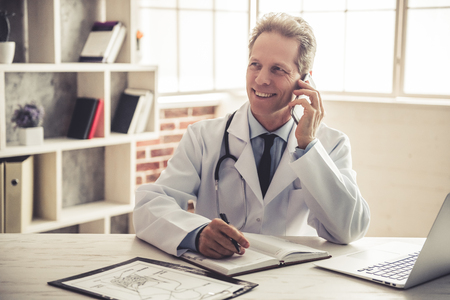 Handsome mature doctor in white coat is talking on the mobile phone, making notes and smiling while working in office Stock Photo