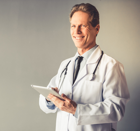Handsome mature doctor in white coat is holding a digital tablet, looking at camera and smiling, on gray background Stock Photo