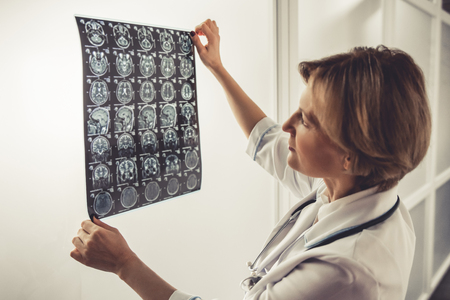 Beautiful mature doctor in white coat is examining x ray images Stock Photo