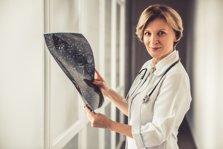 Beautiful mature doctor in white coat is holding x ray image and looking at camera Stock Photo