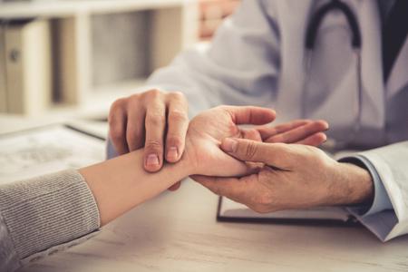 Geerntetes Bild hübschen reifen Doktors im weißen Mantel, der den Impuls des Patienten während der Prüfung in seinem Büro nimmt Standard-Bild