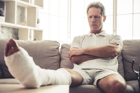 legs folded: Handsome mature man with broken leg in gypsum is sitting seriously with crossed arms on sofa at home Stock Photo