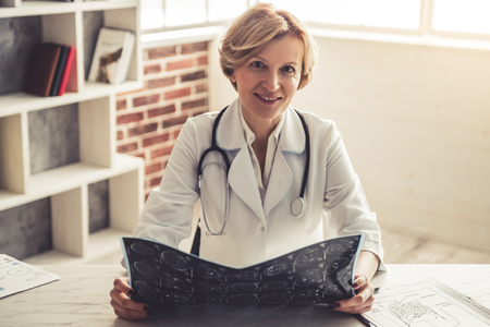 Beautiful mature doctor in white coat is holding x ray image, looking at camera and smiling while sitting in her office