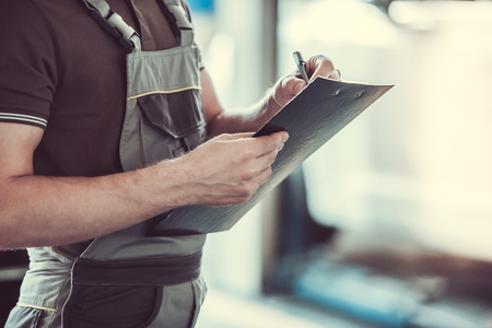 Cropped image of handsome mechanic in uniform making notes while standing in auto service
