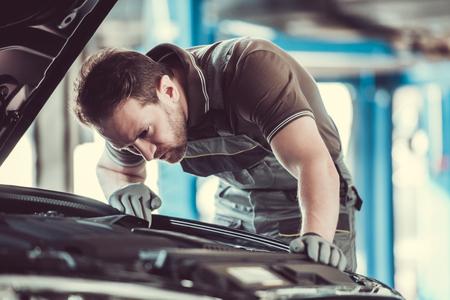 Handsome mechanic in uniform is repairing car in auto service Archivio Fotografico