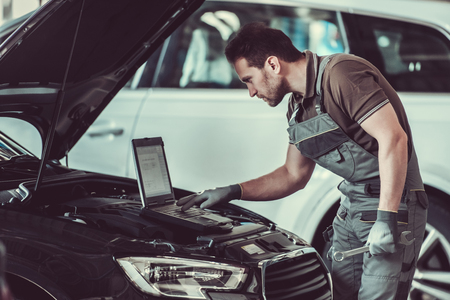Handsome mechanic in uniform is using a laptop while repairing car in auto service