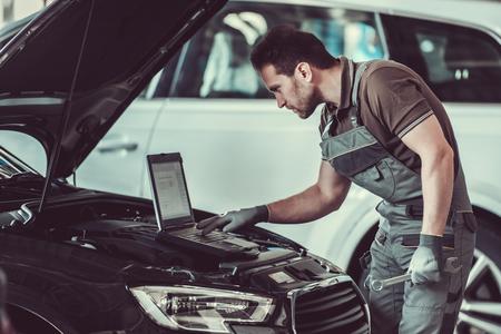 잘 생긴 정비공 제복을 입은 경우 자동 서비스에서 자동차를 수리하는 동안 노트북을 사용하고 있습니다.
