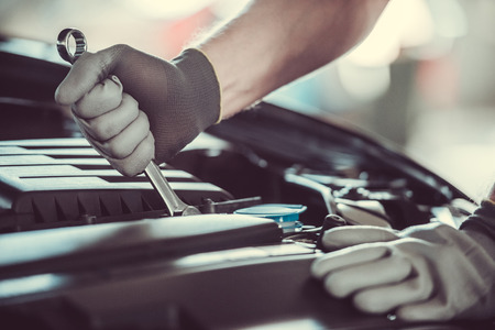 Cropped image of mechanic in working gloves choosing tool while repairing car in auto service