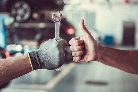 Geholtes Bild der Mechanik, die im Auto Service arbeitet. Man hält einen Schraubenschlüssel, während der andere Okay zeigt
