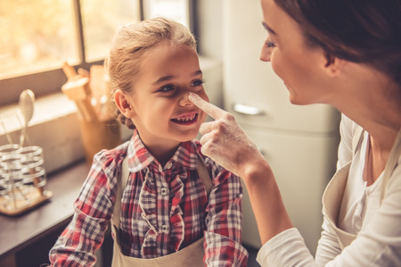 Beautiful young mom and her cute little daughter are playing and smiling while baking in kitchen at home Stock Photo