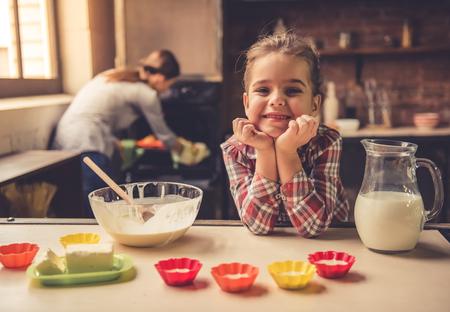 娘と彼女の母親は家庭で焼きます。小さな女の子のカメラ目線と笑みを浮かべながら母親はオーブンをチェック