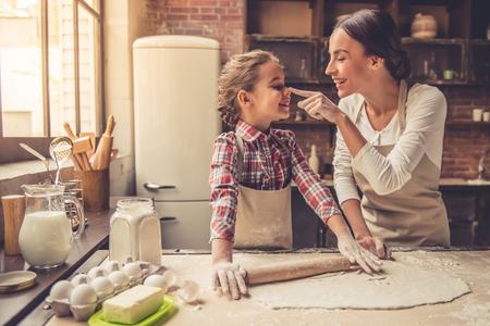 美しい若いお母さんとかわいい小さな娘を弾くことと、自宅のキッチンで焼きながら笑みを浮かべて
