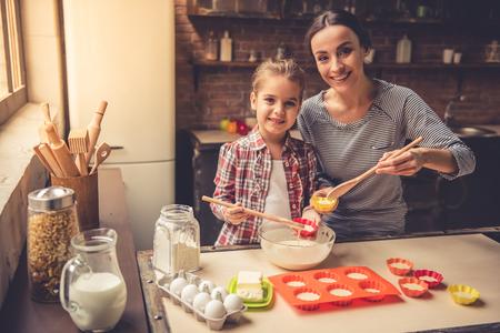 かわいい女の子と彼女の美しい母親は、ベーキング カップ、カメラを見て、自宅を焼きながら笑顔にマフィンのねり粉を spooning します。 写真素材