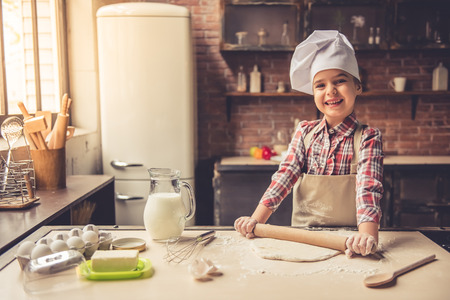 Cute little girl in apron and chef hat is flattening the dough using a rolling pin, looking at camera and smiling while baking Stock Photo